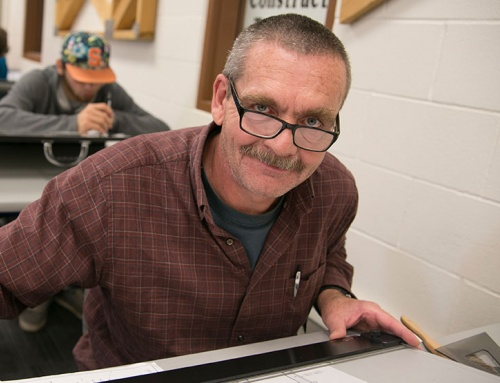 Man with glasses smiling in his Architectural Construction class