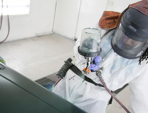 Man using auto body spray painting tools to change the color of a vehicle