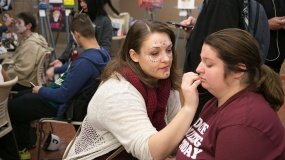 Student paintng the face of another student during a campus event