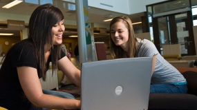 Two young girls sharing a computer screen while smiling