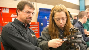 Instructor watches as a young woman completes an auto related task