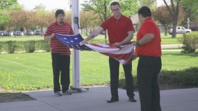 Two students folding flag
